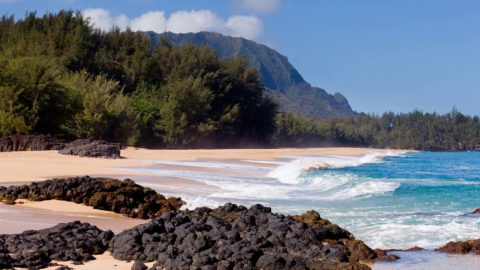 12451387 - waves crash onto lumahai beach on kauai hawaii with na pali coast