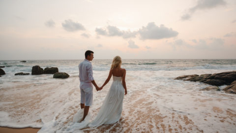 A just married couple stands in the ocean after planning their Hawaii wedding